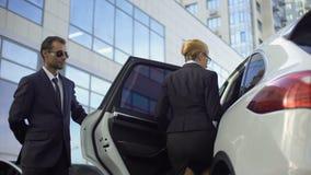 Reunión personal del conductor y puerta de coche de apertura para el jefe de la señora, deberes del escolta almacen de metraje de vídeo