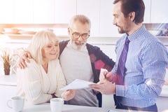 Reunión sonriente positiva de los pares con su agente inmobiliario imagen de archivo