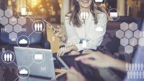 Reunión unívoca Las mujeres tienen smartphone y tableta digital en sus manos Iconos virtuales con las nubes, gente, artilugios Fotos de archivo