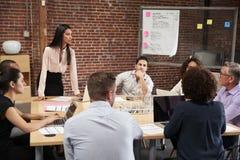 Reuni?n joven de la oficina de Standing And Leading de la empresaria alrededor de la tabla imagenes de archivo