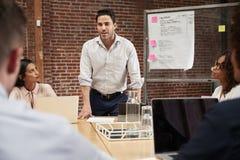 Reuni?n madura de la oficina de Standing And Leading del hombre de negocios alrededor de la tabla imagen de archivo