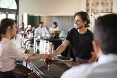 Reuni?o de Serving Two Businesswomen do barman para ap?s bebidas dos trabalhos imagens de stock