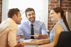 Reunión de los pares con el consejero financiero en oficina Imagen de archivo