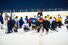 Reunión del equipo de los jugadores del hockey sobre hielo con el instructor Imagen de archivo libre de regalías