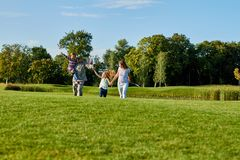 Reunion of american soldier with family. Walking and having fun together on the park grass stock images