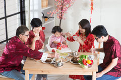 Reunion. Celebrating Chinese New Year, reunion dinner. Asian multi generation family with red cheongsam dining at home Stock Photo