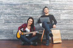 Reunion concept. Happy friends playing the guitar, having fun and communication at home in wooden interior. Reunion concept Stock Image