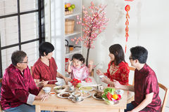 Reunion dinner. Celebrating Chinese New Year, reunion dinner. Happy Asian Chinese multi generation family with red cheongsam dining at home royalty free stock photography