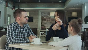 Reunion of happy family in cafe. father, mother and daughter smiling and chatting together. stock video footage