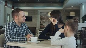 Reunion of happy family in cafe. father, mother and daughter smiling and chatting together. stock photo