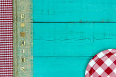 Reunion sign with picnic concept. Red and white checkered plate on antique teal blue wood sign with gingham, rope and burlap REUNION border; above view looking Stock Image