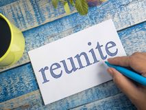 Reunite, Motivational Words Quotes Concept. Reunite, business life motivational inspirational quotes, words typography top view lettering concept stock photo