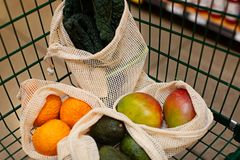 Reusable bag shopping. Reusable produce mesh bags full of fresh vegetables and fruits in the cart at store, zero waste eco friendly plastic free living concept royalty free stock images