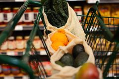 Reusable bag shopping. Reusable produce mesh bags full of fresh vegetables and fruits in the cart at store, zero waste eco friendly plastic free living concept royalty free stock photos