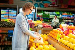 Reusable bag shopping. Young woman holding reusable produce mesh bag full of fresh fruits at the store, zero waste eco friendly plastic free living concept stock photos