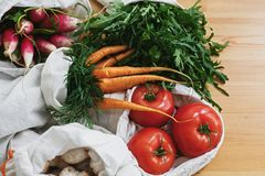 Reusable eco cotton bags with fresh vegetables carrots,tomatoes, arugula, mushrooms from market on wooden table. ban plastic. Sustainable lifestyle. Zero waste stock photos