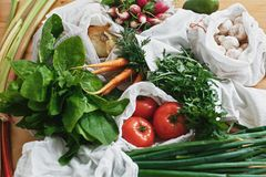 Reusable eco friendly bags with fresh vegetables carrots,tomatoes, spinach,arugula, mushrooms,rhubarb,onions on wooden table. ban. Plastic.Zero waste grocery royalty free stock image