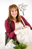 Reusable: Happy to be Using Green Shopping Bags. Series with a woman unpacking groceries and using reusable fabric bags Royalty Free Stock Image