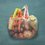 Reusable Net string shopping bag full of various farm organic vegetables from local market on rustic background, top view . Clean royalty free stock photos