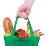 Reusable shopping bag filled with fruits and vegetables. Hand holding a reusable shopping bag filled with fruits and vegetables, isolated on white stock image