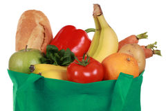 Reusable shopping bag filled with groceries. Groceries in a bag including a bread, fruits and vegetables, isolated on white Royalty Free Stock Image