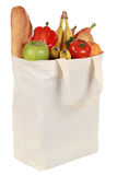 Reusable shopping bag filled with vegetables and fruits. Reusable shopping bag filled with a bread, vegetables and fruits, isolated on white stock image