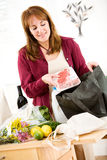Reusable: Unpacking Groceries From Environmentally Green Bag. Series with a woman unpacking groceries and using reusable fabric bags stock photo