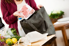 Reusable: Woman Removes Steak from Grocery Bag. Series with a woman unpacking groceries and using reusable fabric bags royalty free stock photography