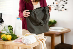 Reusable: Woman Shopper Folding Up Reusable Bags. Series with a woman unpacking groceries and using reusable fabric bags Royalty Free Stock Photo