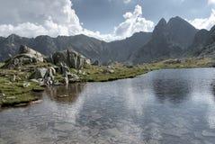 Reusachtig bergmeer onder hoge pieken en witte de zomerwolken Stock Afbeelding