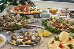 Reusachtig buffet in restaurant met oesters, zeekreeften en kaas stock afbeelding
