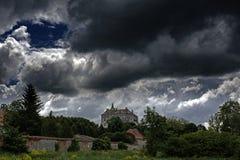 Reusachtig eng oud griezelig kasteel op de bovenkant van de heuvel onder donkere bewolkte hemel Royalty-vrije Stock Foto's