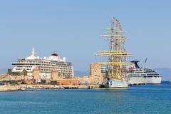Reusachtig varend schip op de achtergrond van twee cruisevoeringen bij de haven Rhodos, Griekenland Stock Foto's