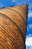 Reusachtige baksteenschoorsteen onder blauwe hemel Stock Foto