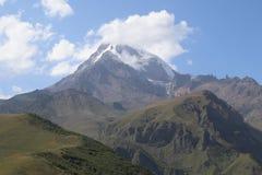 Reusachtige berg Kazbegi en witte wolken omhoog hierboven stock fotografie