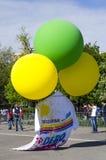Reusachtige die T-shirt door gekleurde ballons wordt opgeheven Stock Foto's