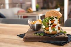 Reusachtige die yummy hamburger op lijst in koffie wordt gediend stock fotografie