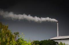 Reusachtige fabrieksschoorsteen die de lucht, Lange schoorsteen verontreinigen die waterdamp en rookverontreiniging uitzenden Royalty-vrije Stock Afbeeldingen