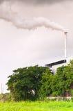 Reusachtige fabrieksschoorsteen die de lucht, Lange schoorsteen verontreinigen die waterdamp en rookverontreiniging uitzenden Stock Fotografie