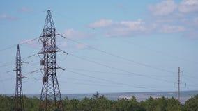 Reusachtige hoogspanningspolen met vele draden die in de afstand gaan stock footage