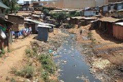 Reusachtige hopen van huisvuil en een vuile rivier in de krottenwijken van Nairobi - één van de slechtste plaatsen in Afrika royalty-vrije stock foto's