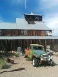 Reusachtige houten schuur met meerdere verdiepingen in woestijn met uitstekende vrachtwagen royalty-vrije stock foto's
