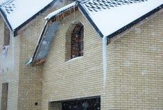 Reusachtige ijskegel op het dak Gevaar sneeuwval stock afbeelding
