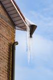Reusachtige ijskegels die van het dak van het huis hangen Stock Foto's