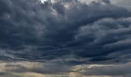 Reusachtige kwade wolken van dark - blauw - grijze kleur met het doordringen van stralen van zon stock foto