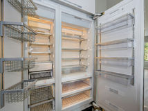 Reusachtige moderne ijskast met lege planken in een keuken Stock Afbeeldingen