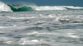 Reusachtige oceaangolvenstroom onder blauwe hemel met wit schuim stock video