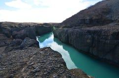 Reusachtige rivier die door grote rotsvormingen gaan in IJsland royalty-vrije stock afbeeldingen