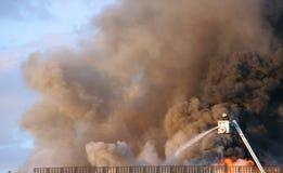 Reusachtige rookpluimen over een gebouw, brandbestrijders bij een lift Royalty-vrije Stock Foto's