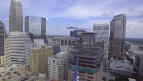 Reusachtige staal moderne stedelijke wolkenkrabbers onder kraanbouwwerf in middencentrum van grote stad in 4k luchtschot stock video